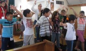 Students at Aprendo Porque Juego Summer Camp practice their summer musical.