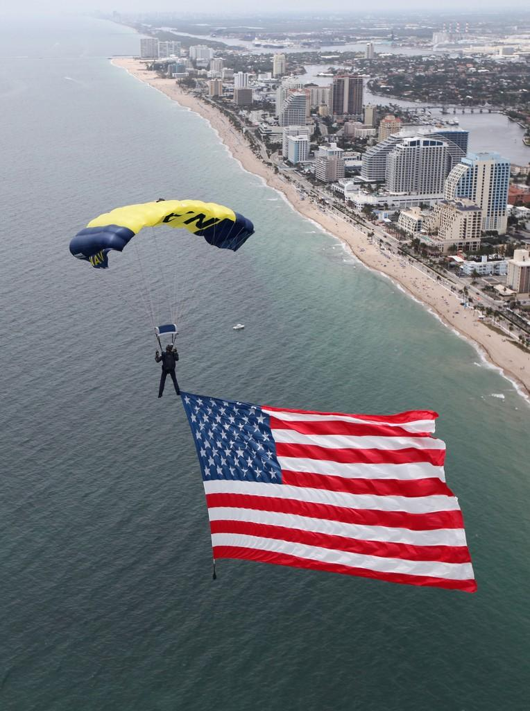 A SEAL on the U.S. Navy parachute demonstration team, the Leap Frogs, flys an 800-square-foot American flag