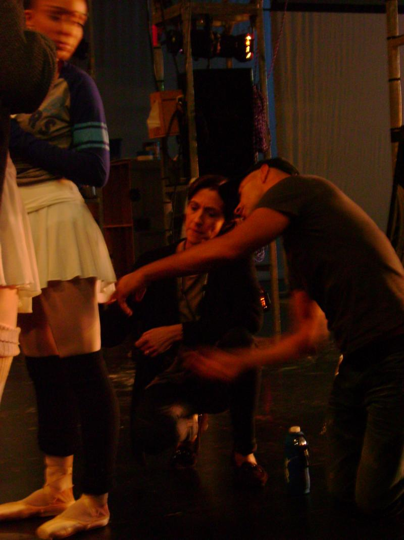 Lourdes Lopez backstage at the Arsht Center fixing a dancer's costume during a rehearsal.