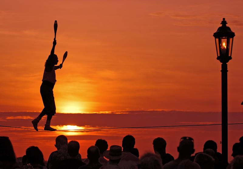 Busker Will Soto walks a tightrope at the sunset celebration in Key West, Fla. The sunset celebration at Mallory Square is a daily ritual for visitors to this subtropical island at the bottom of the Florida Keys island chain.