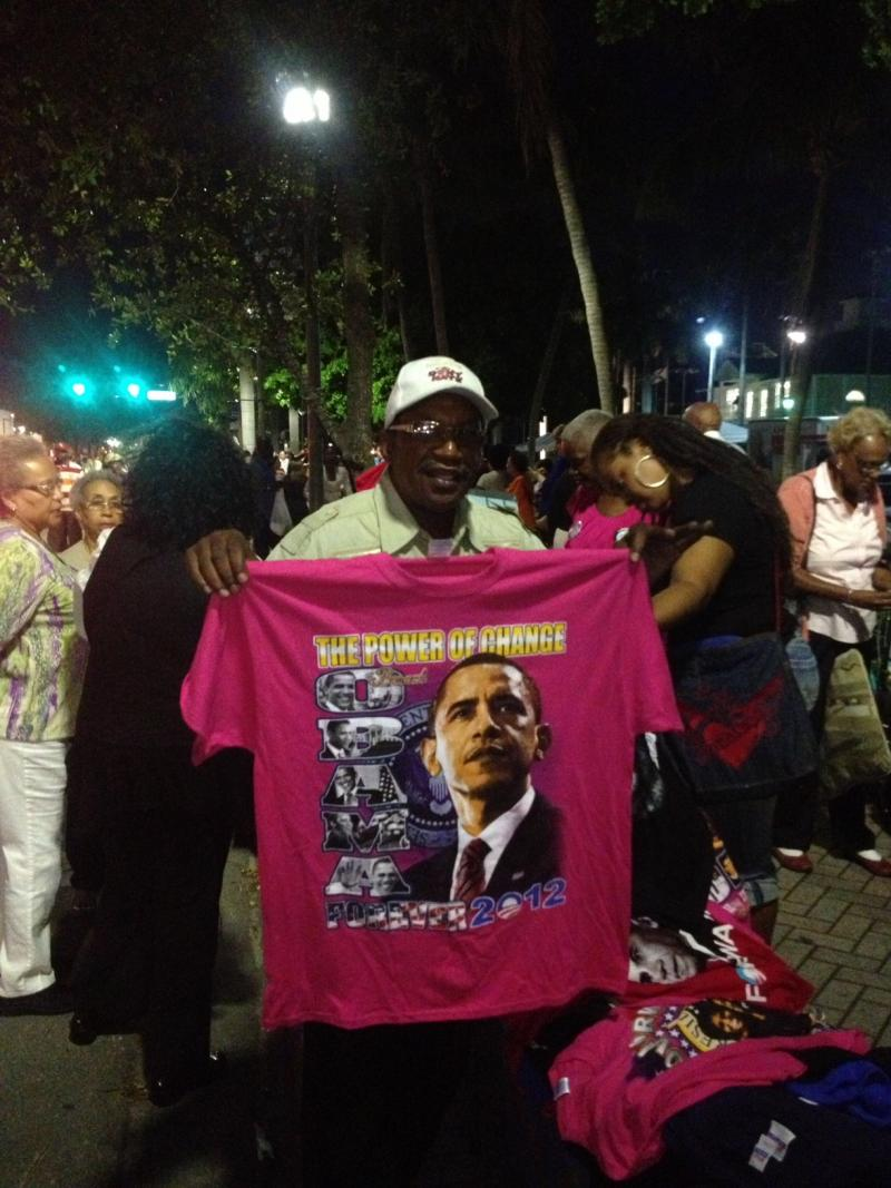 Entrepreneur Under The Lights: The gathering crowd of Obama  supporters is a market for cool t-shirts. The president speaks at 10:15.