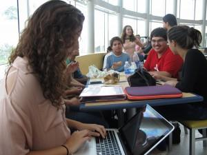 Vanessa Richter, 17, works on her online summer course as her friends eat lunch at a food court.