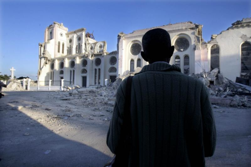 A man stands and prays outside the collapsed National Cathedral in Port-au-Prince, on Sunday Jan. 16, 2010.
