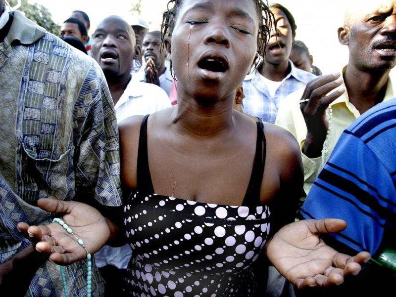 A young woman prays at the site of the collapsed National Cathedral in Port-au-Prince, just days after the earthquake.