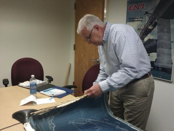 Dennis Fernandez of FDOT flips through some of the original blueprints of the bridge.
