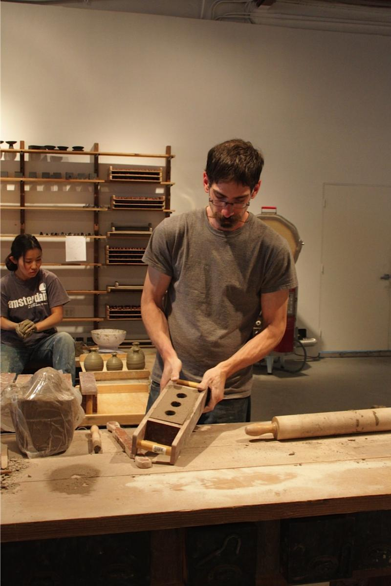 Matthew Dercole uses a mold to make bricks.