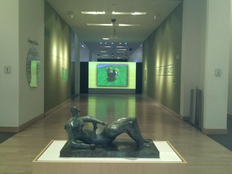 In the foreground is a sculpture by British artist Henry Moore. In the background is a large montage of video games at the Boca Raton Museum of Art.