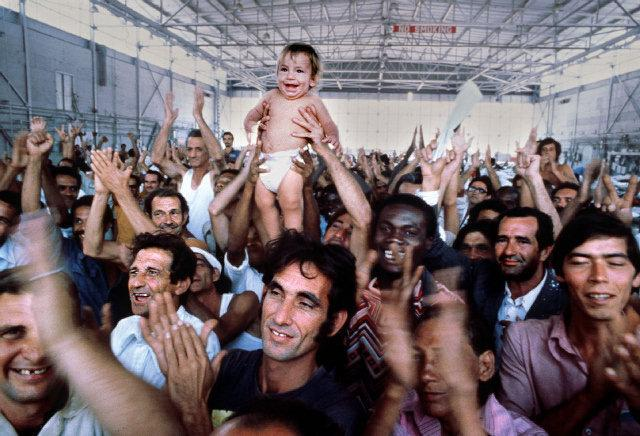 "In 1980, Chapman took one of the most iconic photos from the Mariel Boat Lift. He was in a military hanger. ""This guy from the military came out and said, 'Welcome to America.' And these people, they just erupted with joy."""