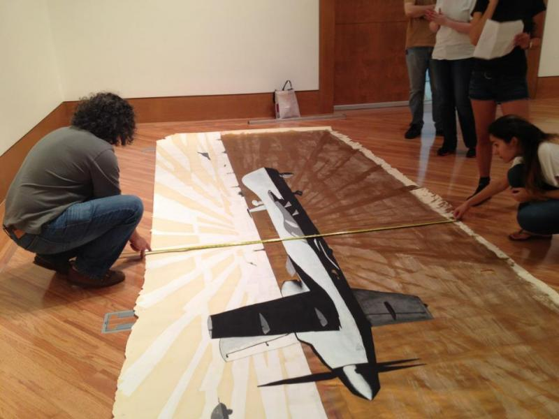 Glexis Novoa installing his piece with the student curators on the third floor of the Frost Museum