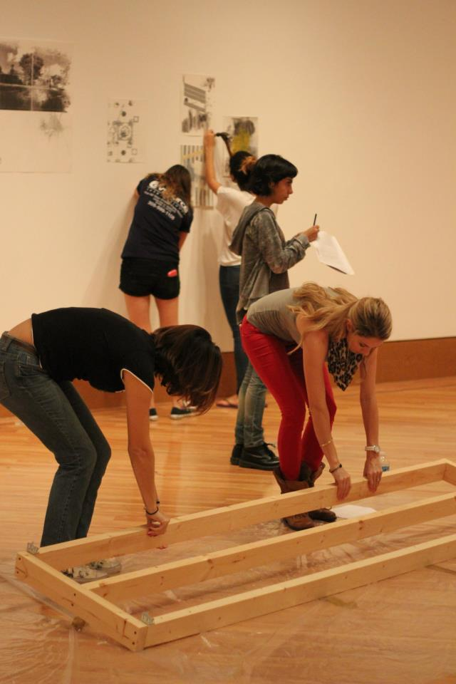 Students manuvering Leyden Rodriguez-Casanova's installation pieces