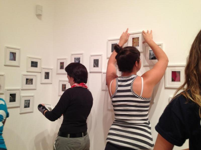 Students assisting Maria Martinez-Canas install her 50 mini photographs