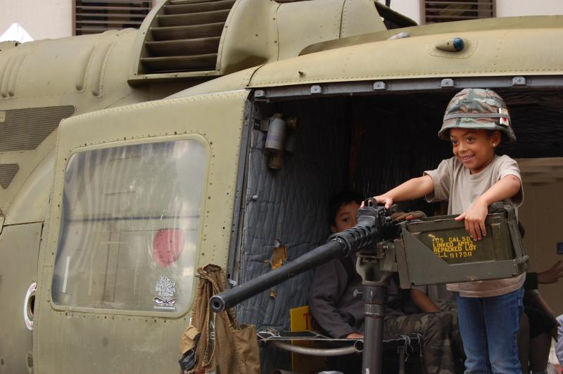 Kid plays with the machine gun mounted on a Vietnam War era helicopter.