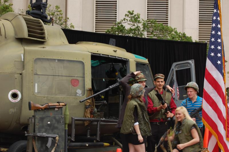 Adults pose for pictures in front of the vintage Navy helicopter with weapons and gear from the Vietnam War.
