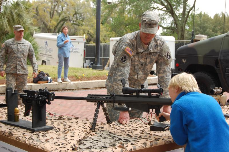 A kid looks through the scope of a .50 caliber semi-automatic sniper rifle.
