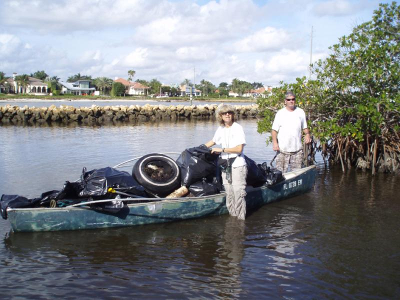 ERM volunteers pull old tires and other debris from a Palm Beach County-managed natural area.