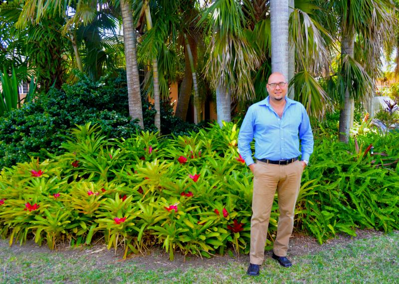 "Extension agent Guillermo Salazar of the Miami-Dade County Extension Office, stands in front of a ""native"" Florida garden, with a bromelliad 'Neoregelia compacta' patch in the backround."