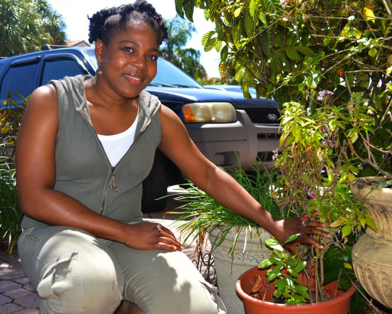 Carol Xavier of the U.S. Virgin Islands, next to her bay leaf plant. The sapling was brought over to South Florida in a suitcase.