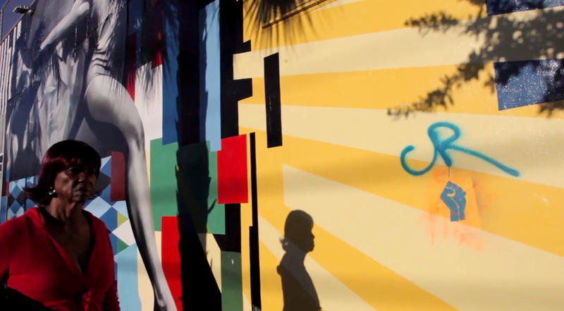 In this screenshot from the film Right to Wynwood, this unidentified resident is walking by Eduardo Kobra's mural on 2nd Avenue.