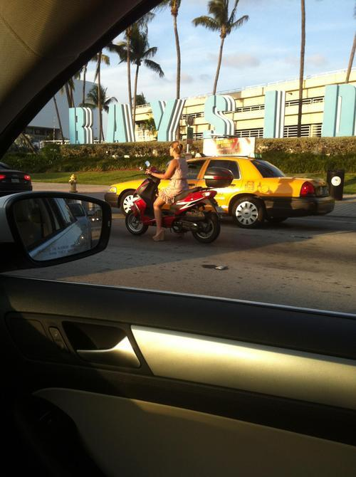 A woman on a motorcycle  in a sundress, platform sandals,  sans helmet, smoking a cigar,  driving past Bayside.  That's so Miami.