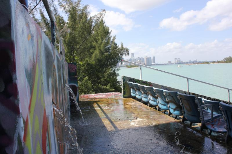 After pulling a clogged drain at the stadium, water flows out toward the basin with Downtown Miami in the background