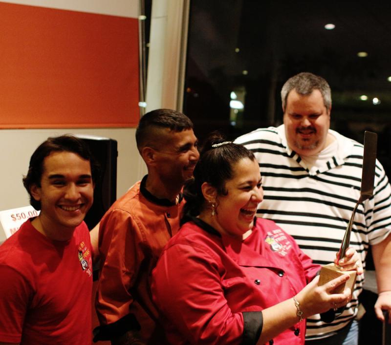 El Rey de Las Fritas claims the engraved spatula trophy at the Frita Showdown, as Sef Gonzalez (Burger Beast) looks on.