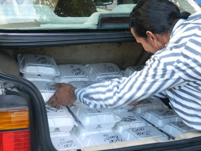 Free meals for the homeless are unloaded from the trunk of Gloria Lewis' car. The waitress from Fort Lauderdale has been cooking over 100 meals a week, not enough for the people who line up to get them in downtown Fort Lauderdale.