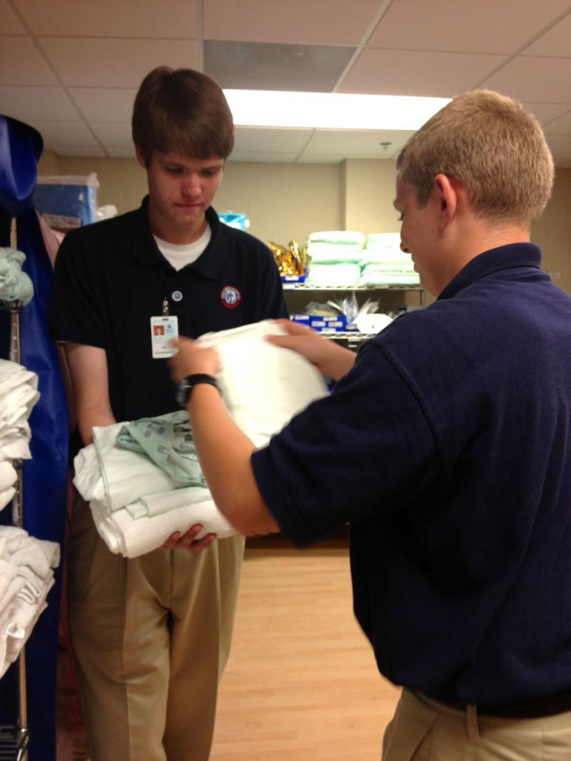 Volunteer Will Hinson, left, and Connor Smith, right, prepare sheets and blankets for a patient's room.