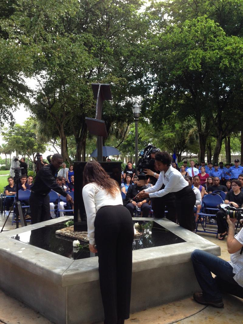 Miami-Dade College students light candles to dedicate the memorial.