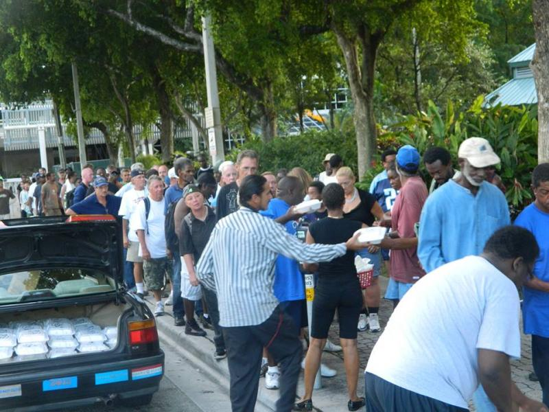 Gloria Lewis' meals are distributed to a line of hungry people in downtown Fort Lauderdale.