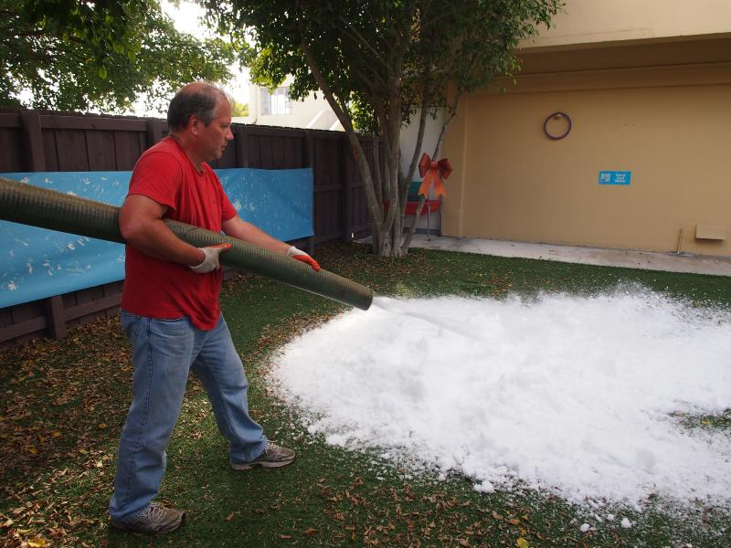 Marty Enis, shown above, owner of Florida Ice Manufacturing, comes down from Westford, Massachusetts every year to deliver snow from Thanksgiving through February. Here, he's blowing the snow at the preschool.