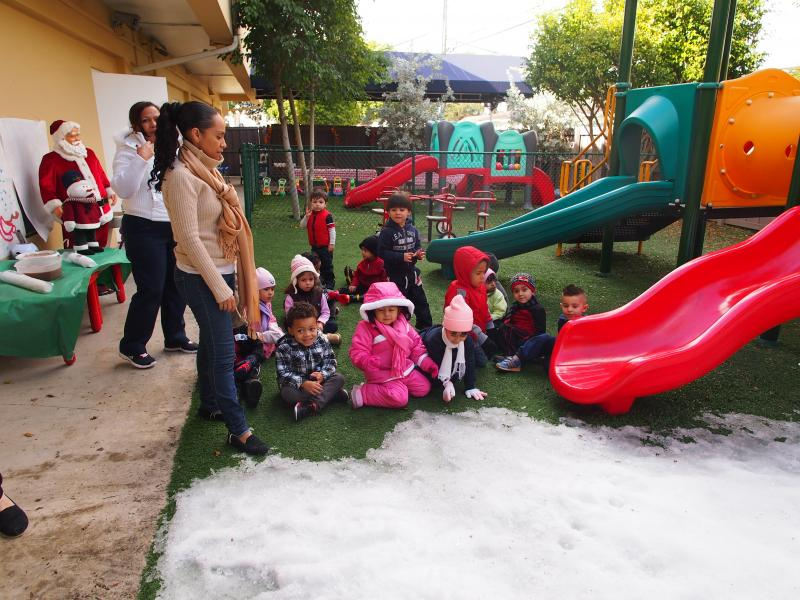 The older children, here a group of 2- to 3-year-olds, are excitedly waiting to play in the snow at a preschool in Little Havana.