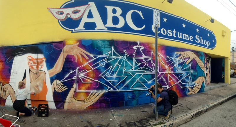 Kazilla spray-painting a mural on ABC Costume Shop.