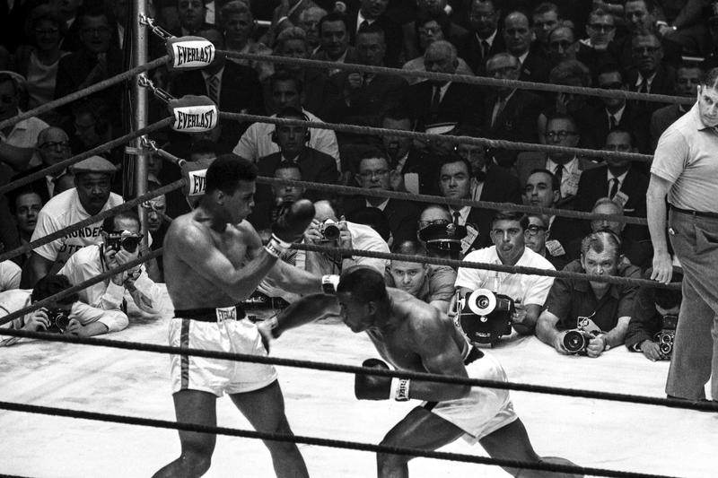 Liston lands a straight right to the hip (an illegal blow), while Clay counters with a left hook