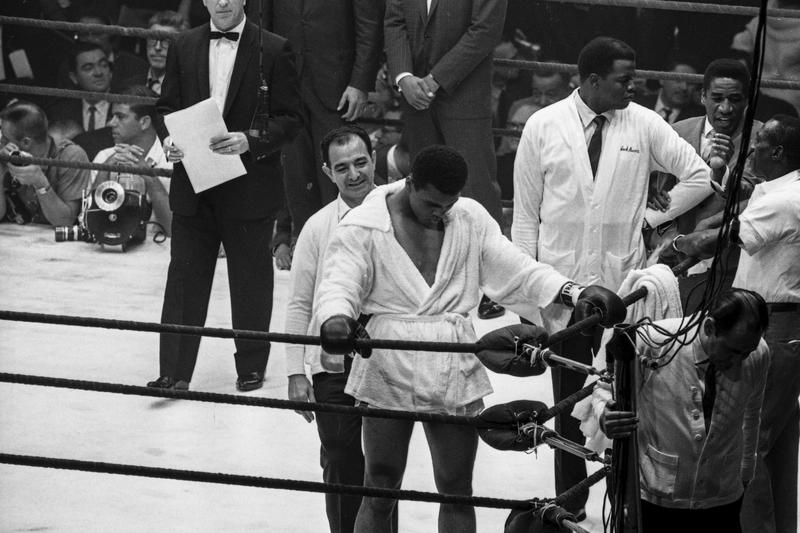 Clay takes a moment to pray.  Pictured: Angelo Dundee, Bundini Brown, welterweight champion Luis Manual Rodriguez, Luis Sarria and Ferdie Pacheco crowd the corner.