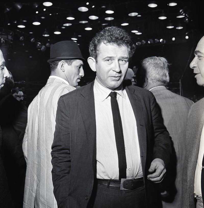 Ali fan and renown author Norman Mailer at the 1964 match. Mailer would later write The Fight, a book about the Ali vs. Foreman match in Zaire. Behind him is hard-punching middle-weight contender Florentino Fernández.
