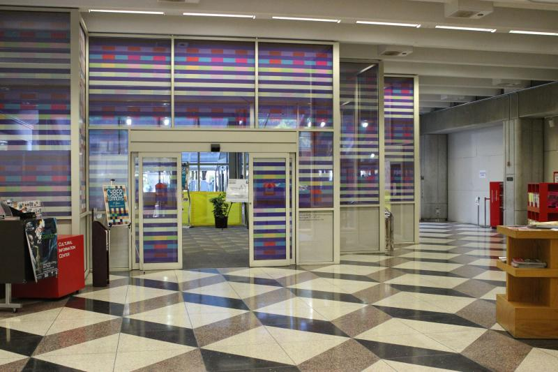 After heading up the ramp, you'll come across colorful glass. This is the exterior of the first floor computer lab. Outside of the frame and to the right is the library's auditorium.