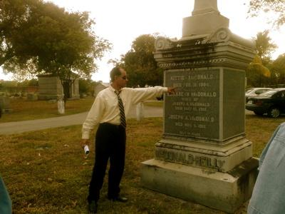 Dr. Paul George points to a tombstone the city cemetery. Many of Miami's original movers and shakers are buried here.