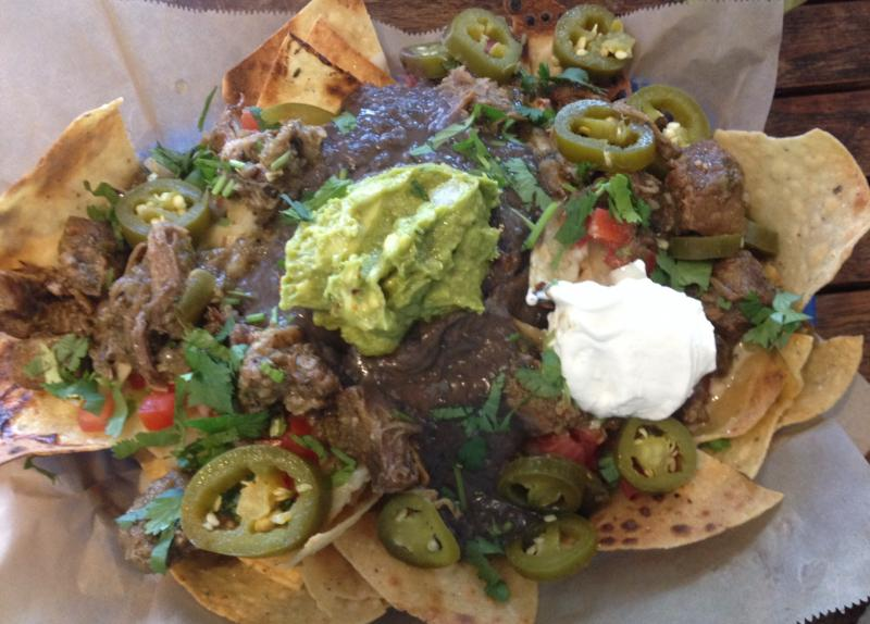 A plate of crispy nachos topped with jalapeños, sour cream, and guacamole.