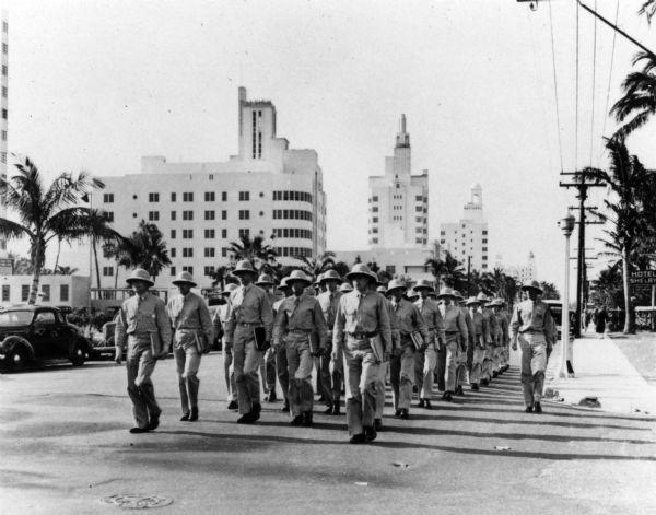 Servicemen march along Collins Avenue in Miami Beach. Circa 1944.