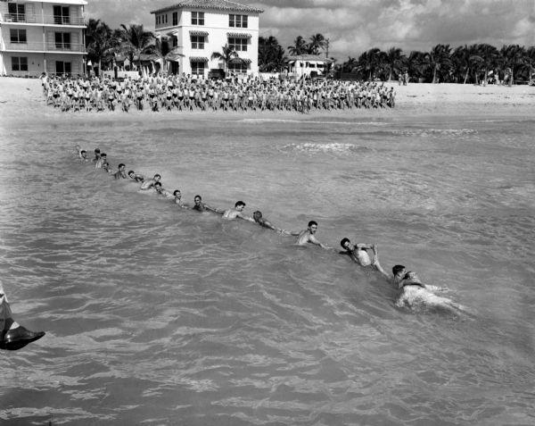 Officers candidate school trainees form a human chain during survival training practice in the surf off Miami Beach. Circa 1943.