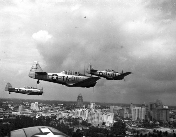 Three Air Force planes take part in a simulated air attack over downtown Miami, 1946.