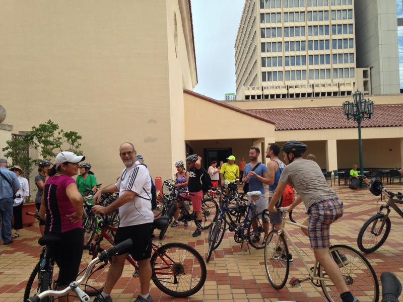 """Cyclists wait outside HistoryMiami for the first scene of """"History On Wheels""""."""