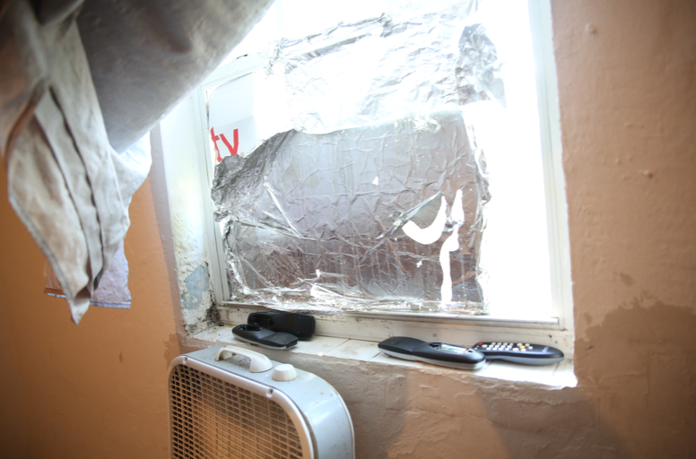 Rodents and bugs crawl freely through Wayne Caroll's apartment window because it has no screen. Caroll tried to fashion a barrier out of cardboard and aluminum foil.