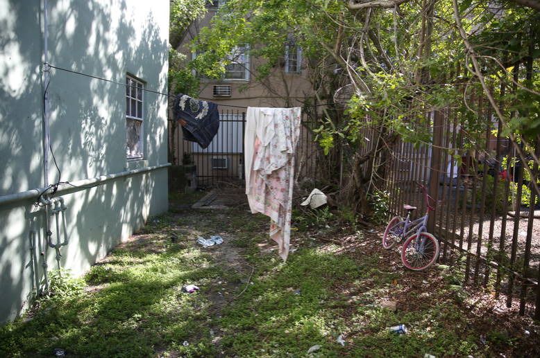 Wayne Caroll and his nephews go to the bathroom on this littered stretch of grass behind their apartment. Caroll's toilet overflows if he flushes it.