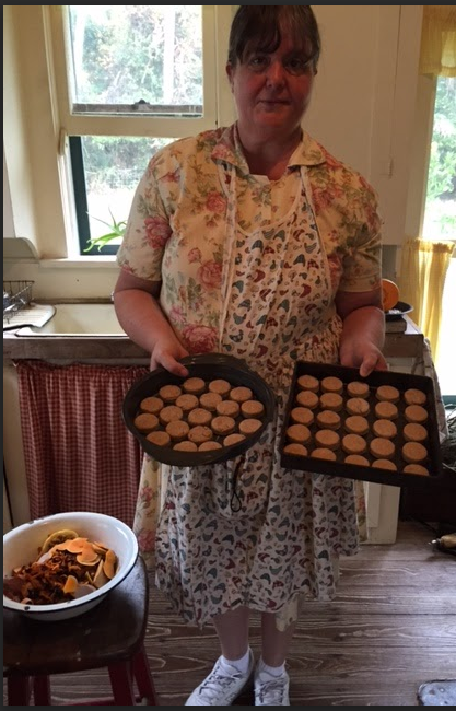 One of the Wood Stove Sisters in period costume bakes in Cross Creek's kitchen
