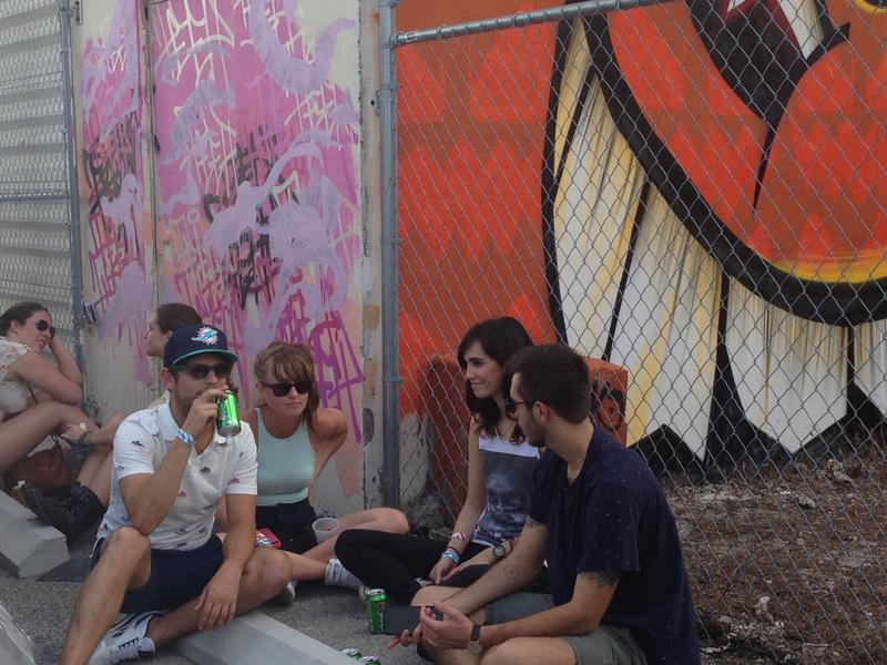 A group of block party attendees gather around the wall murals at the Leah art district.