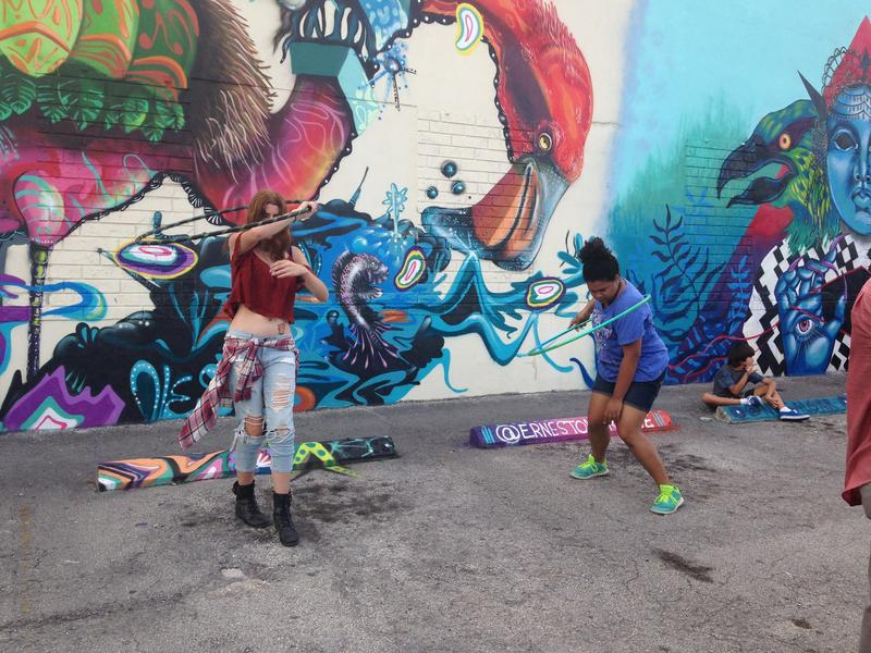Girls hula hooping in front of one of the murals in the Leah art district.