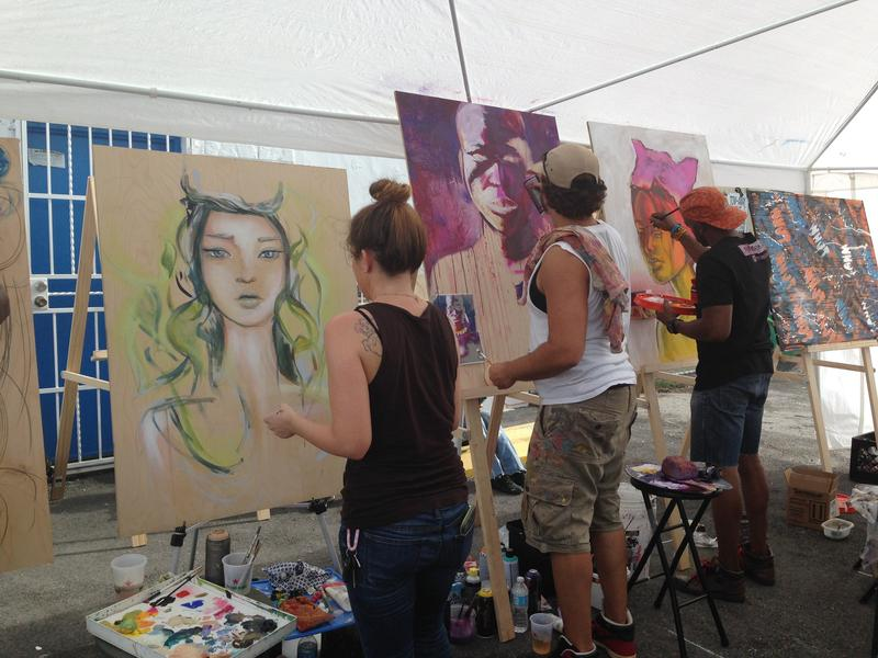 A line of artists paint portraits at the Leah art district opening.