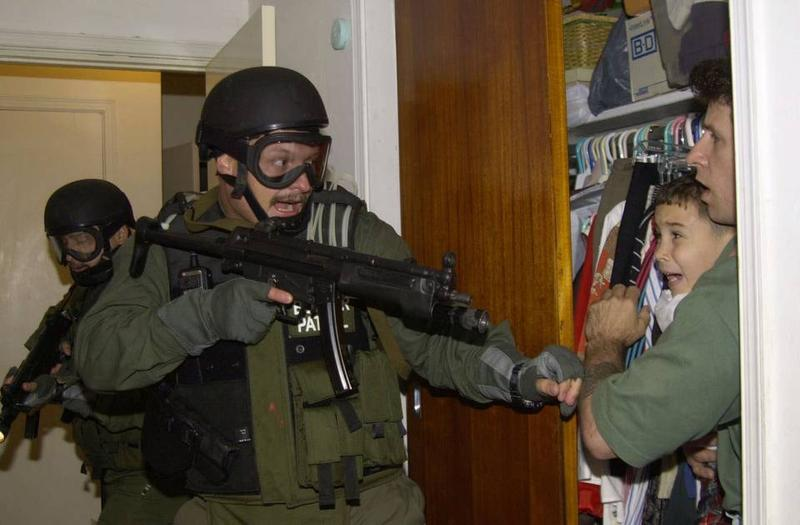 An armed U.S. federal agent storms the house in Little Havana on April 22, 2000, to seize Elian Gonzalez, who was in the arms of Donato Dalrymple, the man who'd rescued the boy from the ocean five months earlier.
