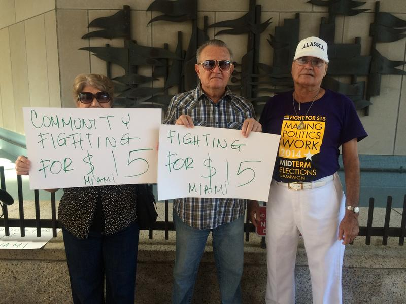 Retiree Rafael Nuñez, right, supports young low-wage workers at a conference Thursday.